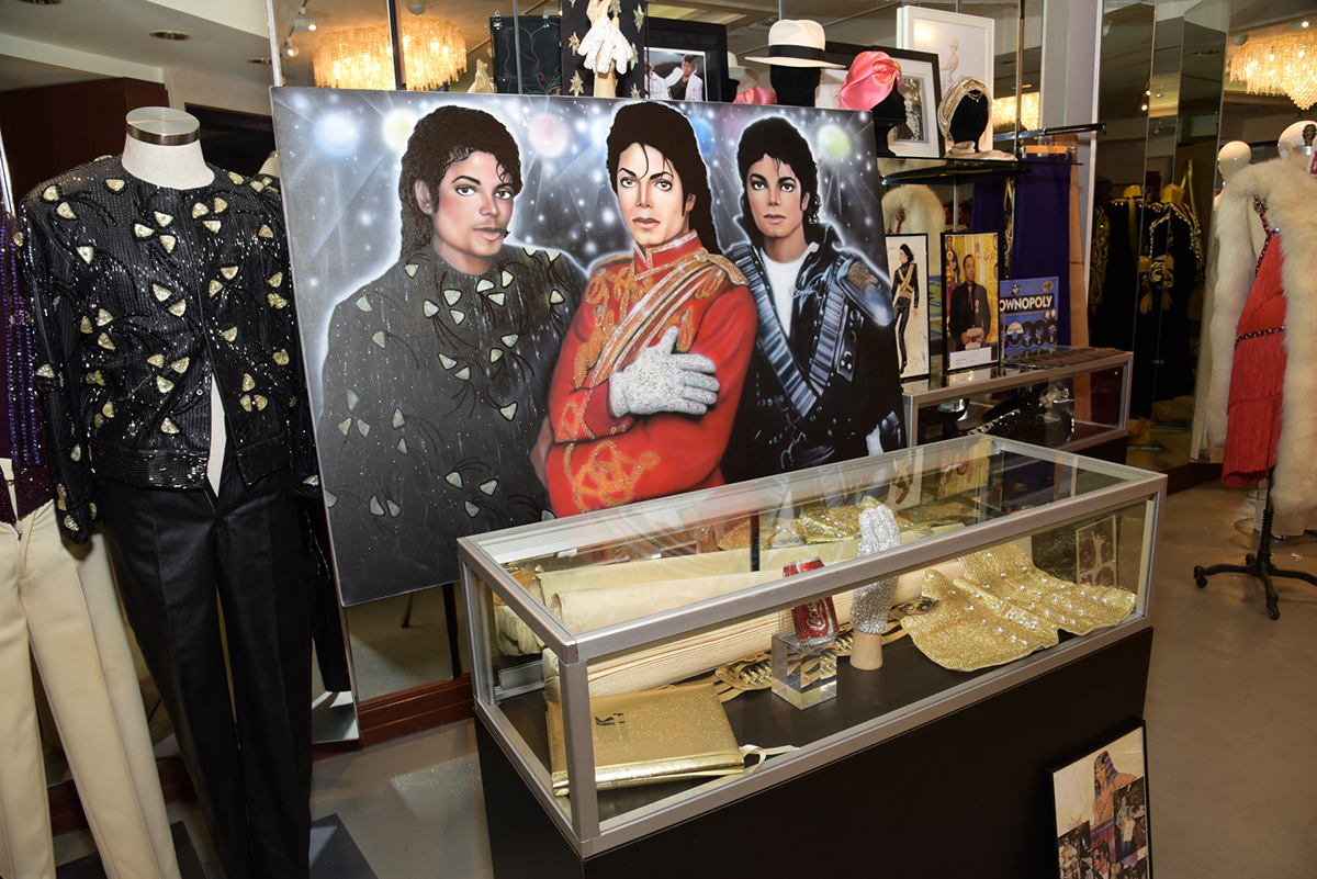 """(l to r) A Michael Jackson jacket, Leon Jones painting and Marilyn Monroe """"The Seven Year Itch"""" dress pattern. The display case includes Michael Jackson's glove, a Coca Cola handbag, chest strap and 2001 calendar."""