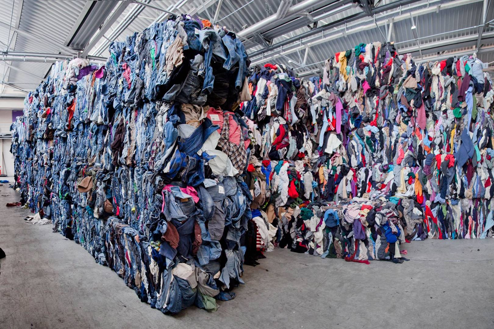 Mountains of sorted clothing at one of the facilities where H&M recycles clothing. The company was accused of burning 60 tons of recyclable garments in 2017. Credit: GQ
