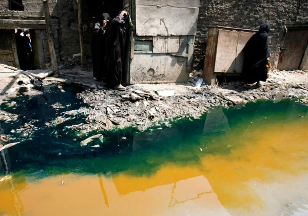 Women walk past tannery wastewater that is being pumped from a factory straight into the street, in Cairo's Ain el-Sirra district. Credit: Reuters