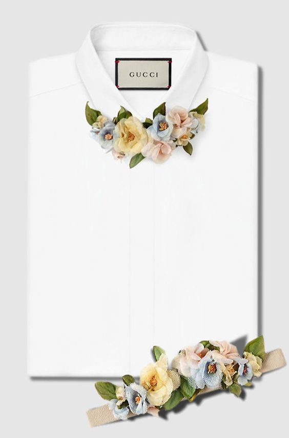 Caption: A crisp, white dresshirt, folded in a square. Instead of a tie, though, the shirt has a collar of fabric flowers and leaves in pastel earthtones. The shirt/collar was designed by Gucci.