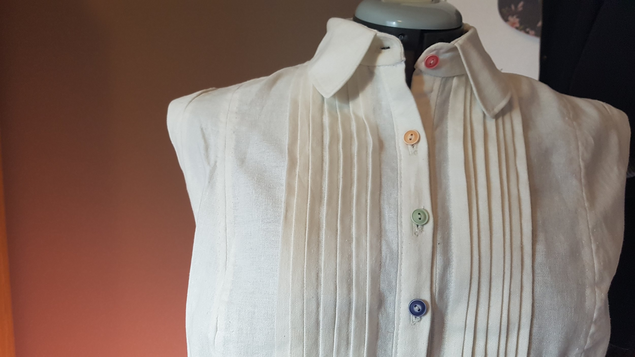 Caption: A close up of the Amelia Blouse from the collar down to the bustline. The four buttons of the placket are, respectively, pastel pink, an earthone yellow, pastel green, and a soft navy blue. The finish on them makes them look like glazed pottery.