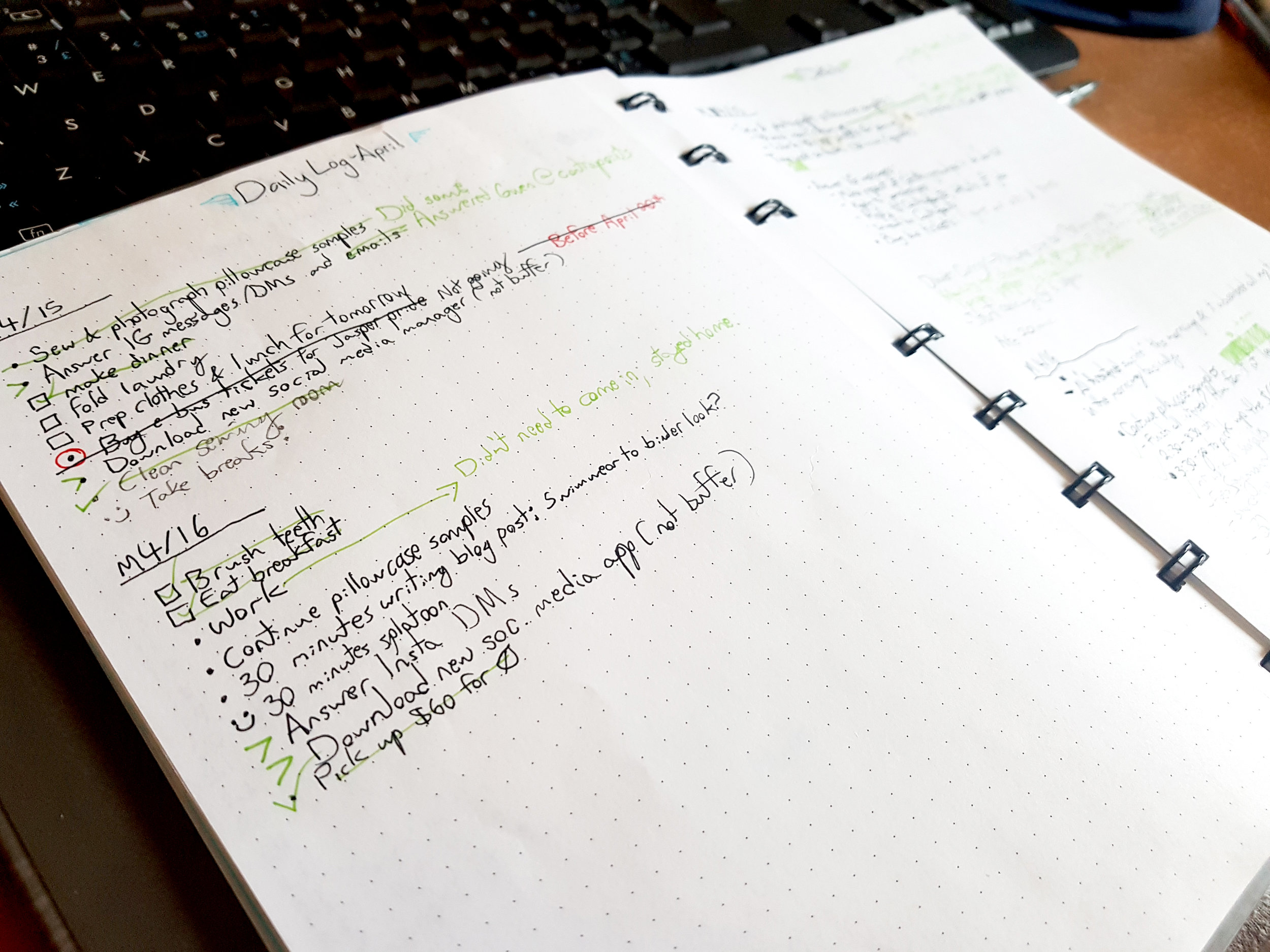 A bullet journal laid open in front of a black keyboard. The bullet journal has a couple task lists, and the writing uses black, red, kiwi green, and cyan pens.