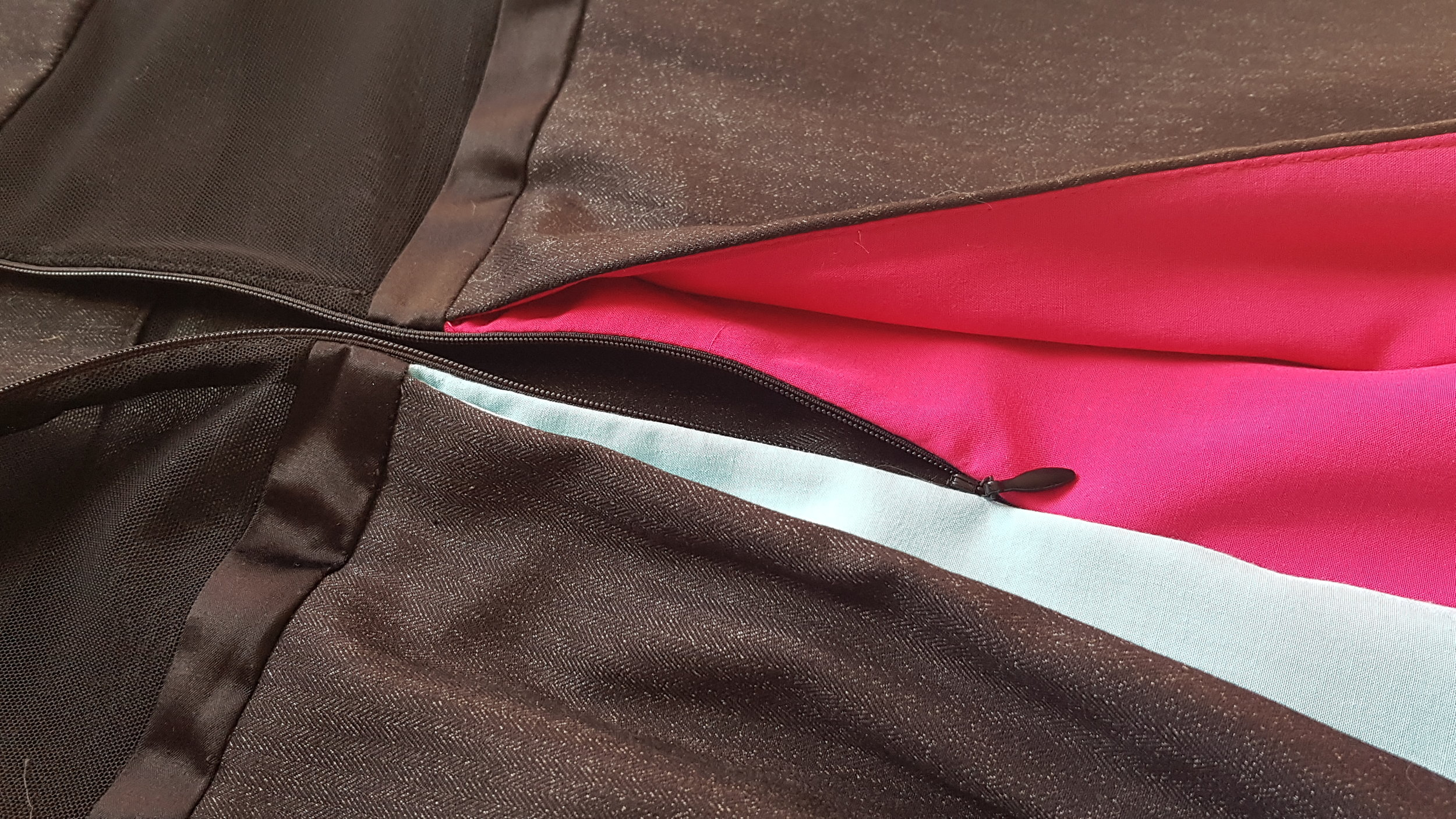 Caption: a close-up shot of the back of the Todrick dress, which has an inverted box pleat at the centre back. There is an invisible zipper that extends into the box pleat, which is split down the middle in two colours: bright pink and light blue. The bodice is separated by a black satin 'belt', with the lower bodice made of black mesh and the upper made of the same heather black herringbone suiting as the rest of the dress.