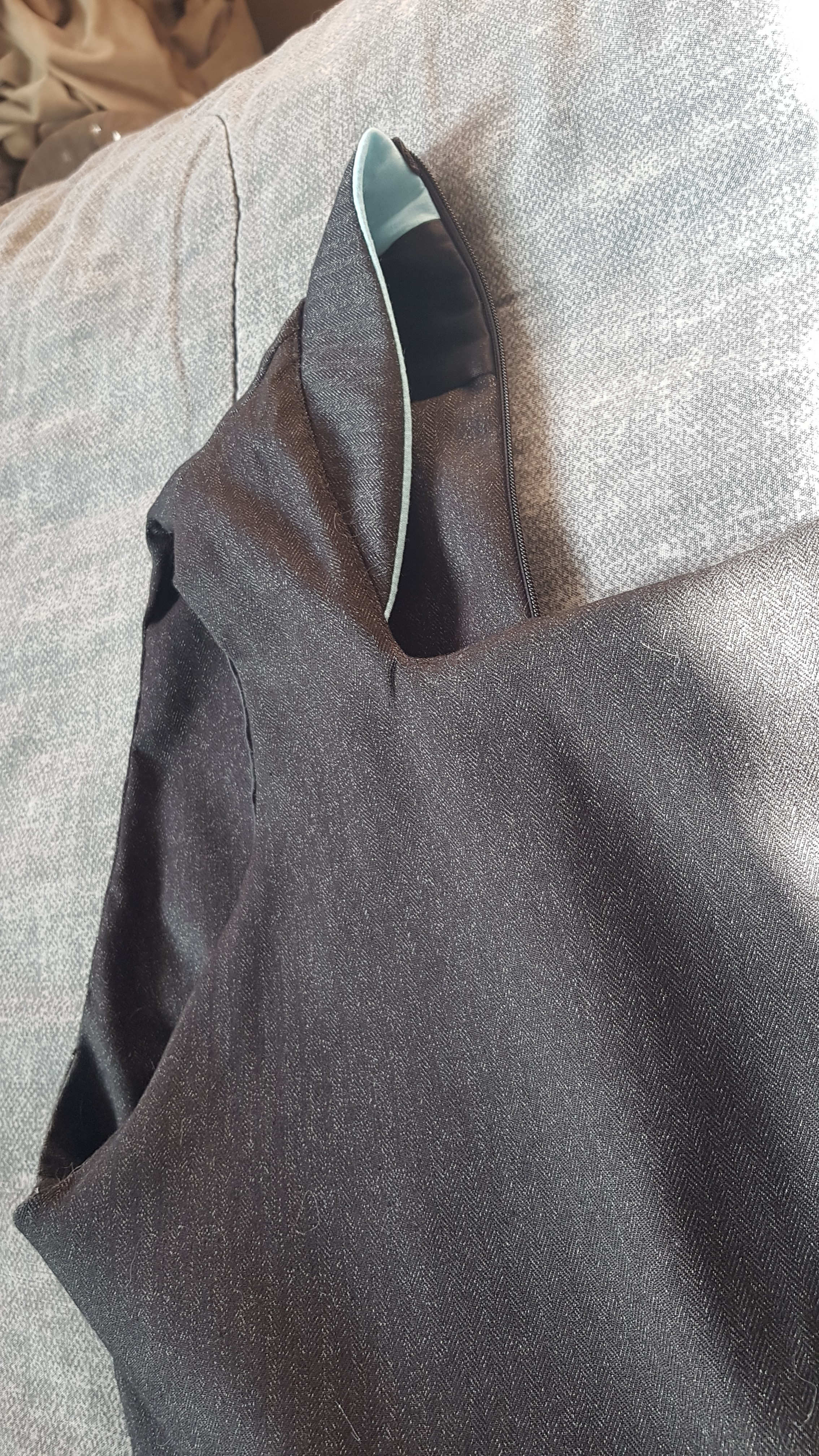 A close up of the inside of the todrick dress bodice. which has been lined up to the satin waist belt with the same dark herringbone suiting as the rest of the main dress fabric.