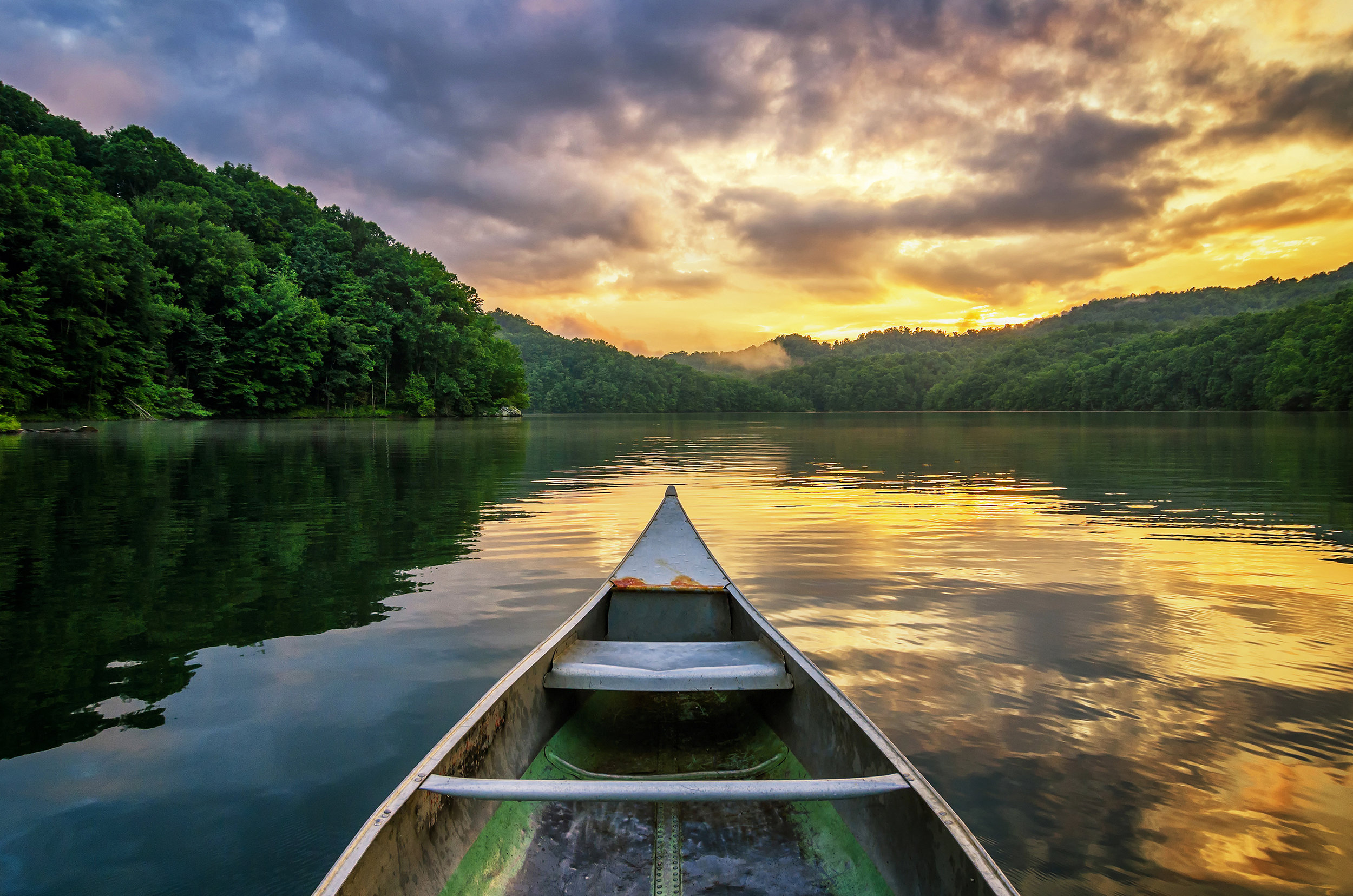 A dramatic sunset from an old canoe on a clam mountain lake in the Appalachian Mountains of Kentucky.jpg
