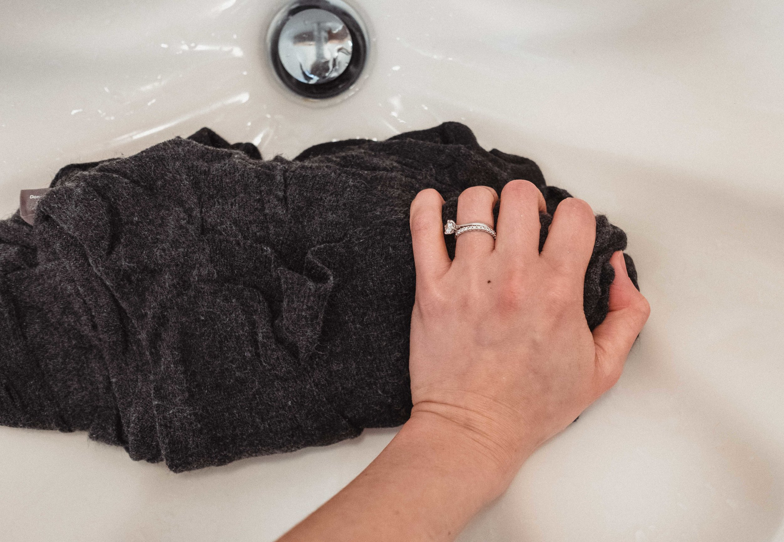 Step 4:  after you have drained the water, keeping the sweater in its natural shape, gently squeeze out the water. Again, do NOT wring out the sweater. It does not have to be completely dry at this point and wringing the sweater will cause stretching in the material.