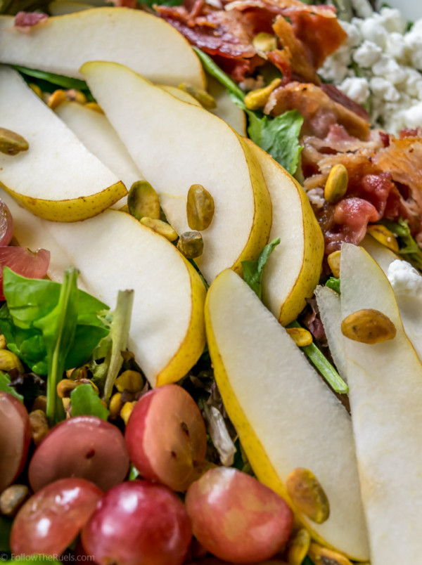 Salad topped with pears and bacon.