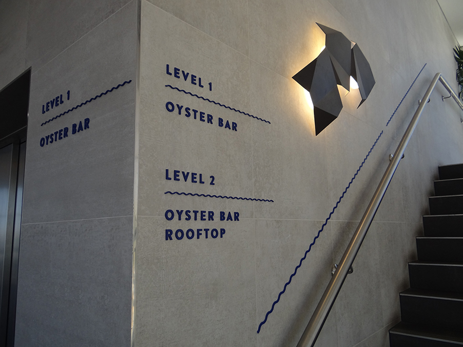 WAY FINDING SIGNS   Laser cut acrylic letters and decorative detail, fixed directly to tiled walls and placed on entrance level of restaurant.
