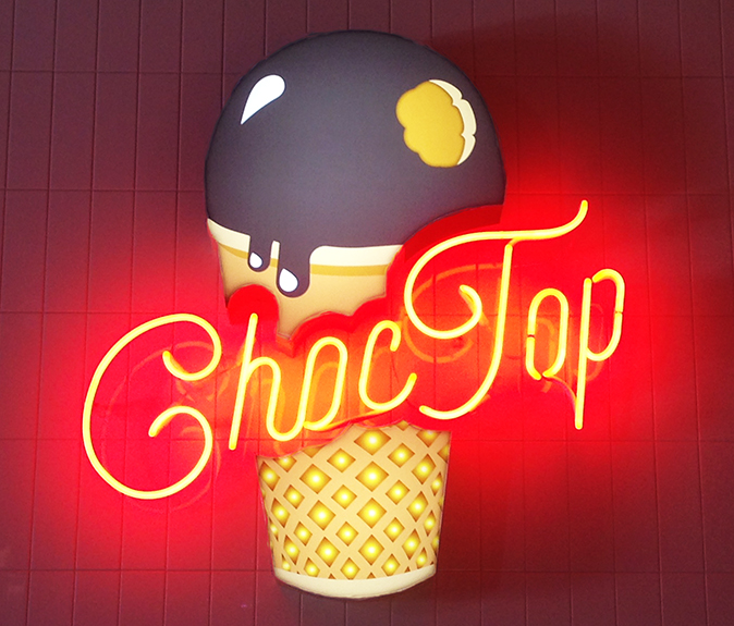 CHOC TOP NEON SIGN  The center piece for the snacks area was the Choc Top neon sign. A fabricated acrylic ice-cream cone with digitally printed detail and internally illuminated with LEDS. Open red neon letters.