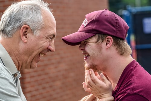 Image: Older man smiling with a younger man who has Down Syndrome