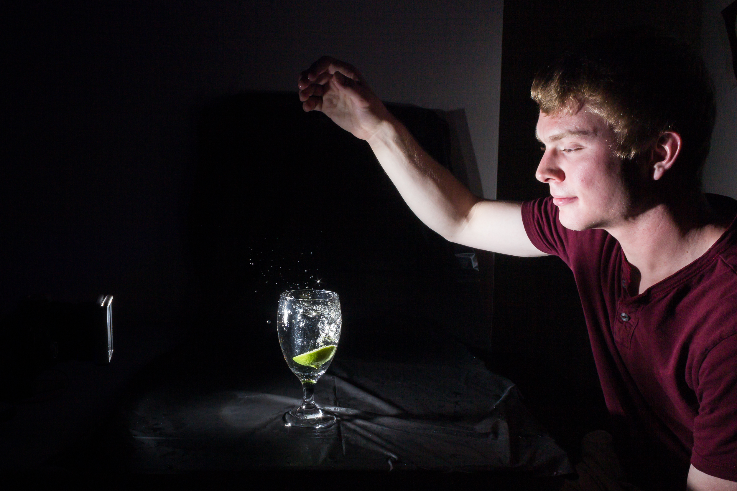 Me in 2014 dropping fruit into a wine glass. I programmed the software to fire the flash a few milliseconds after detecting the splash. I found that the images were more interesting with this configuration. The delay gave the splash above the glass and the bubbles inside the glass more time to develop into interesting shapes.