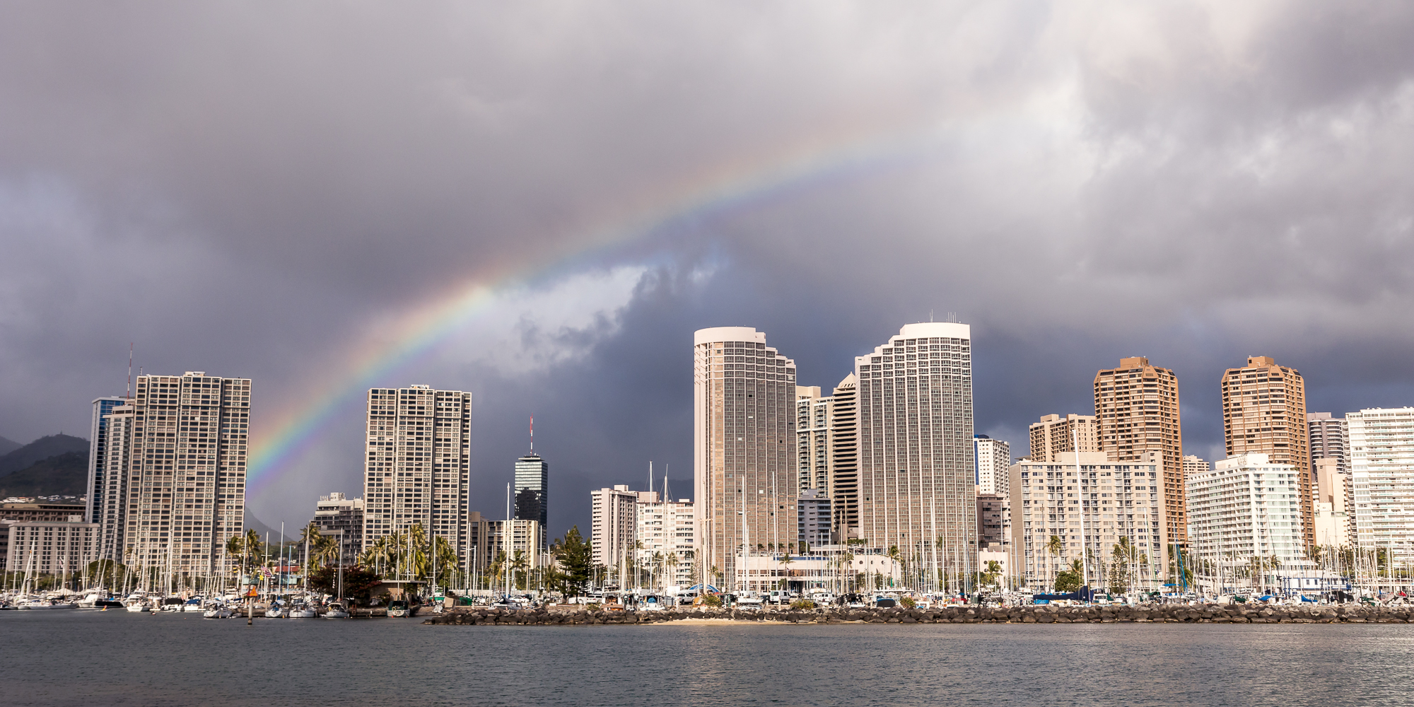 A rainbow arches over Waikiki during the day.