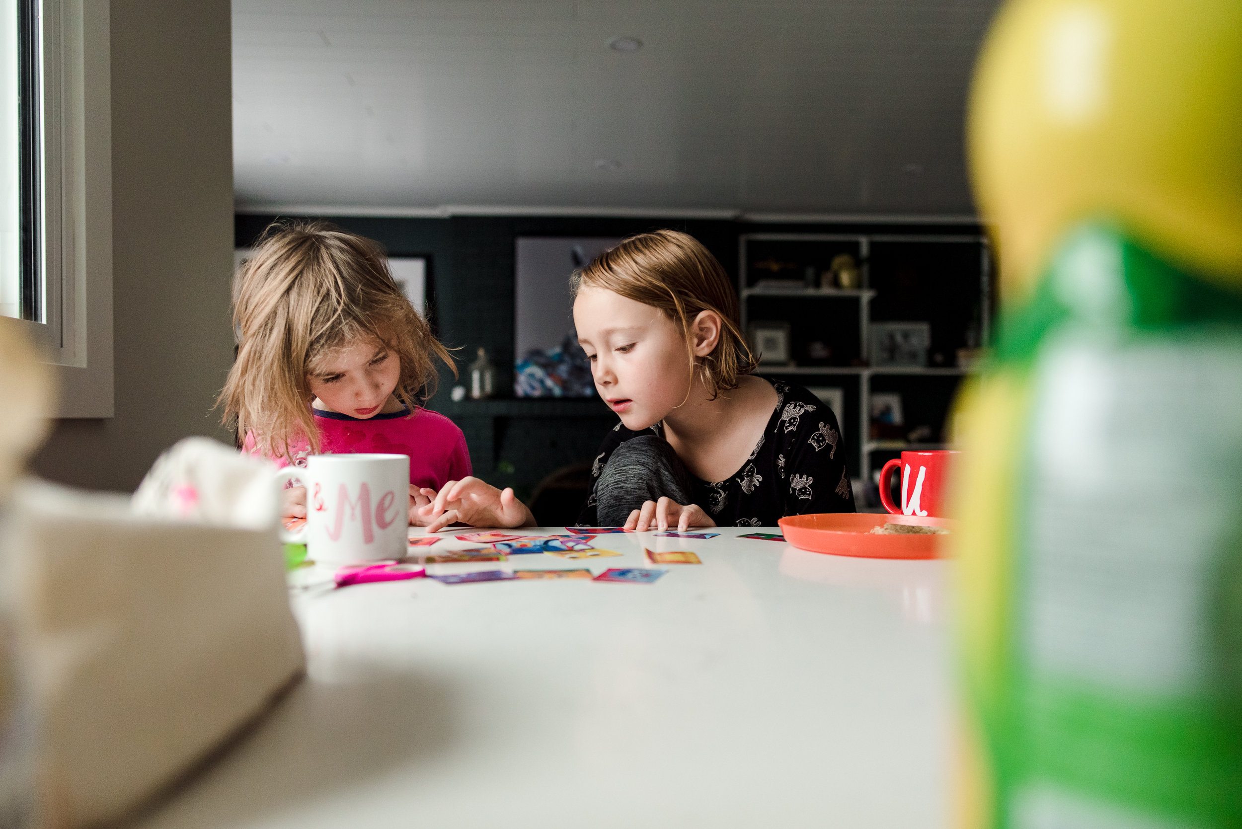 Sisters sit at a kitchen counter as part of a photography series. Photography tutorials.
