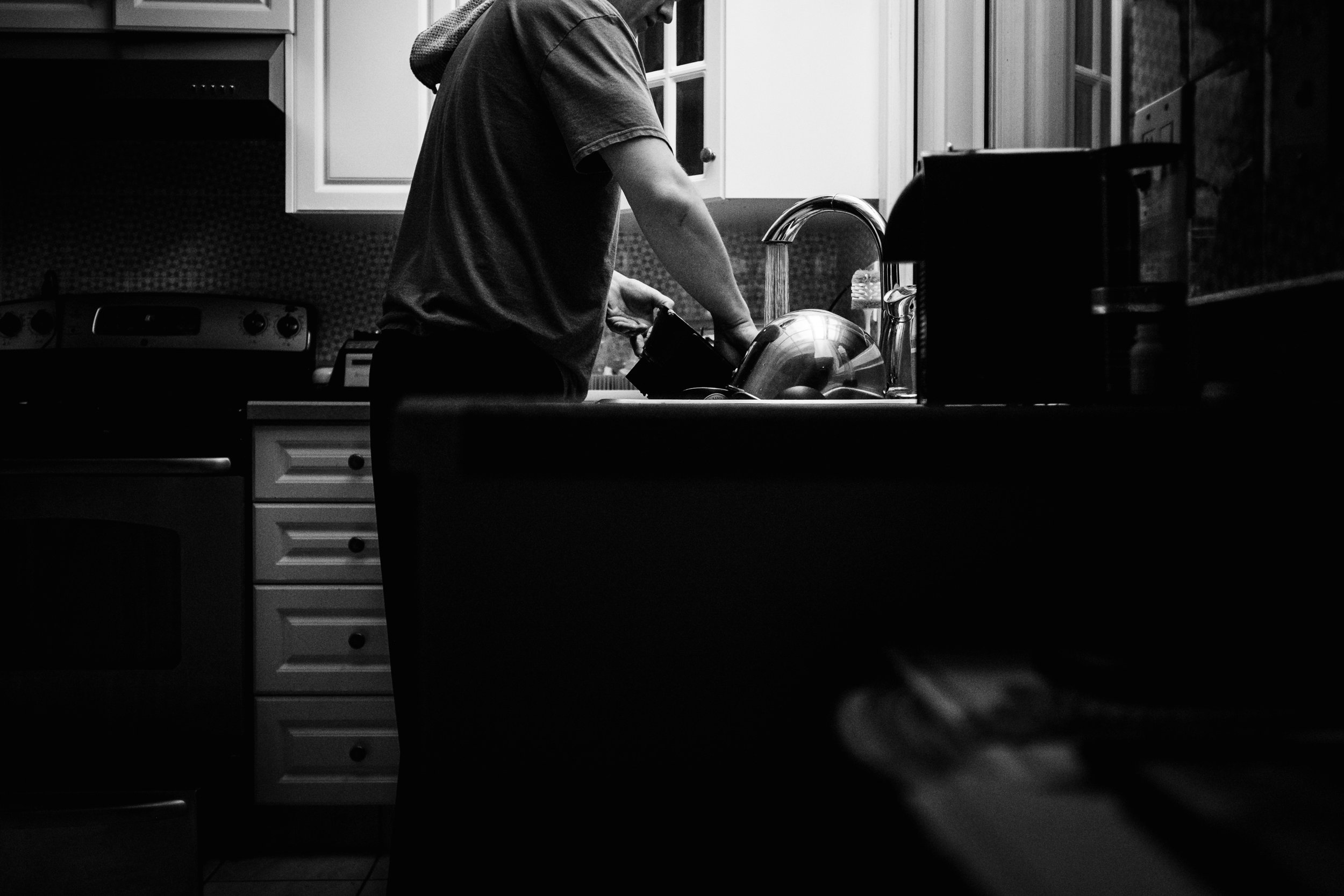 a man washes dishes at the kitchen sink .jpg