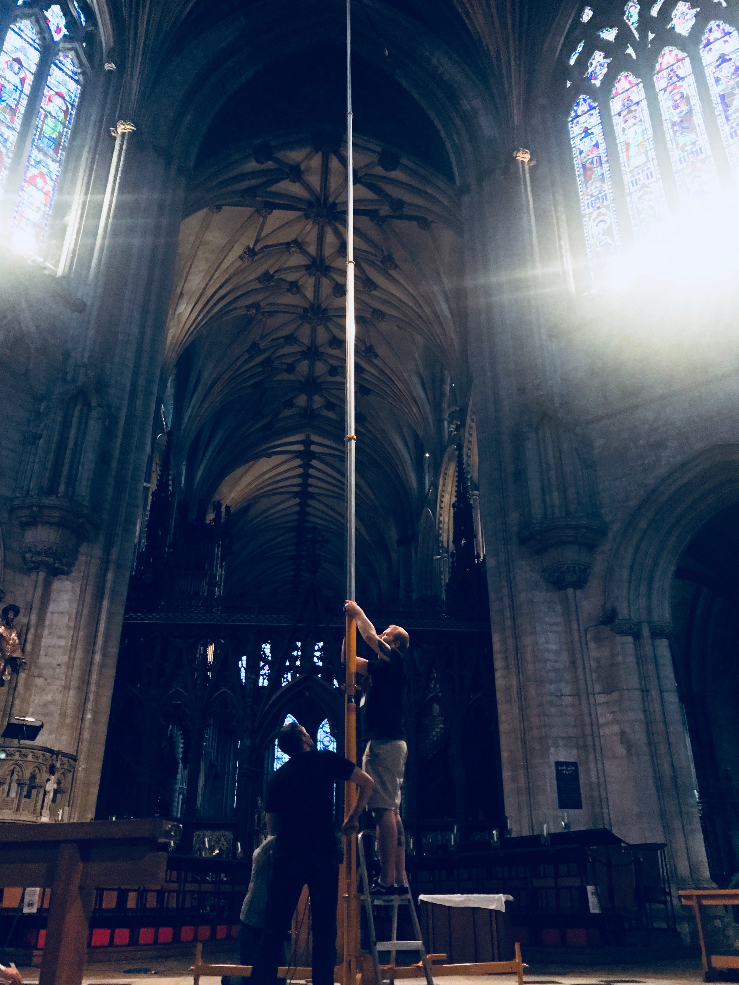 Abbey Road engineers Lewis Jones and Matt Jones erect a 50 foot mast under the tower of Ely Cathedral - the microphones placed at the top will help to capture the cavernous acoustic of this ancient building