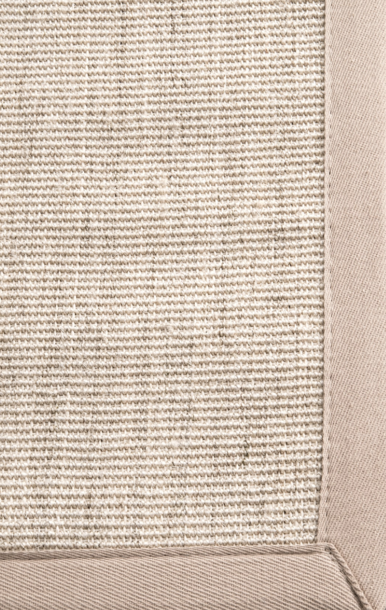 """If you find a rug you love, but it's not quite large enough for your space, consider layering it over a larger seagrass or sisal area rug. These rugs can be relatively inexpensive and provide a nice """"frame"""" for that one-of-a-kind rug you love."""