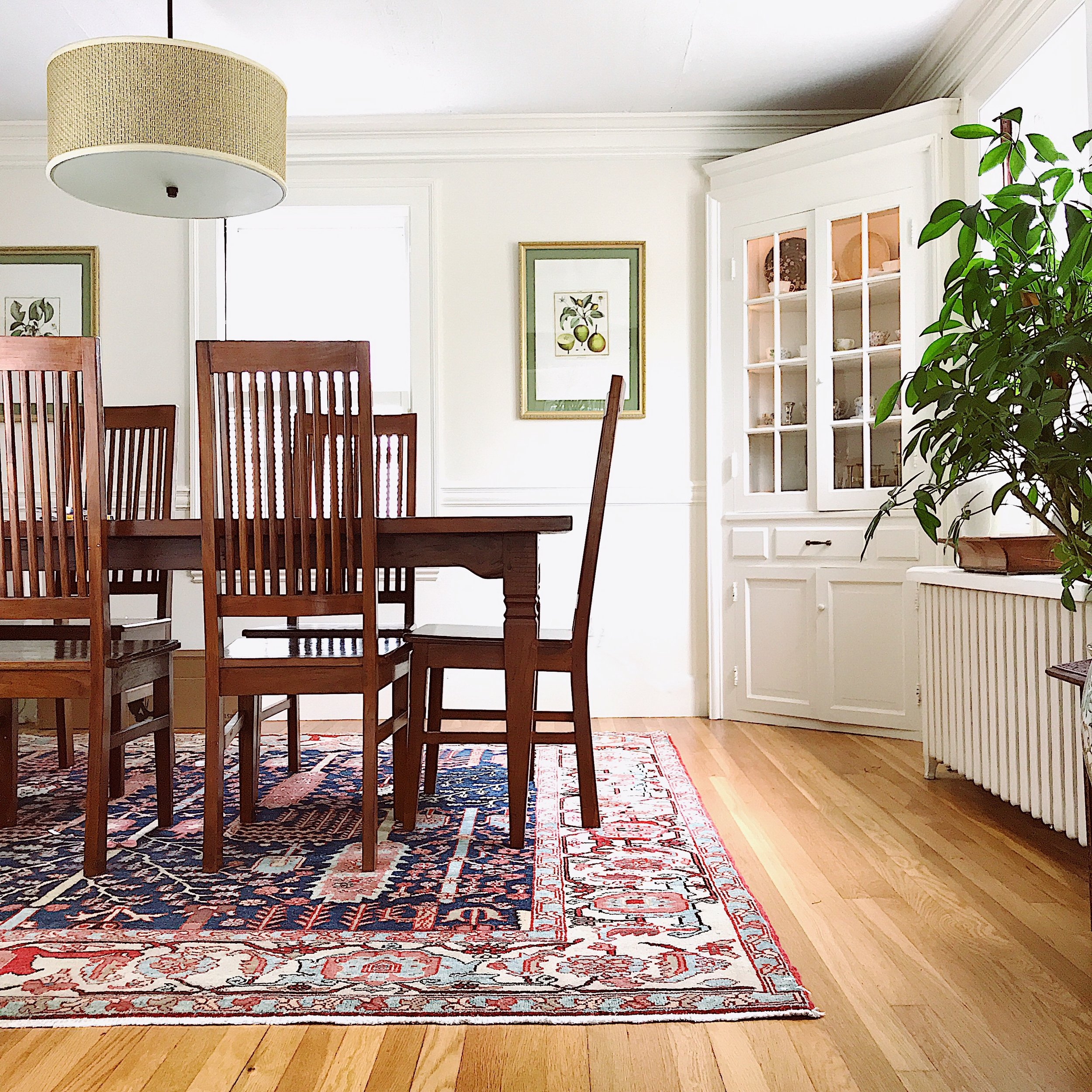 A thrifted rug and vintage botanical prints round out the estate sale finds in the dining room.