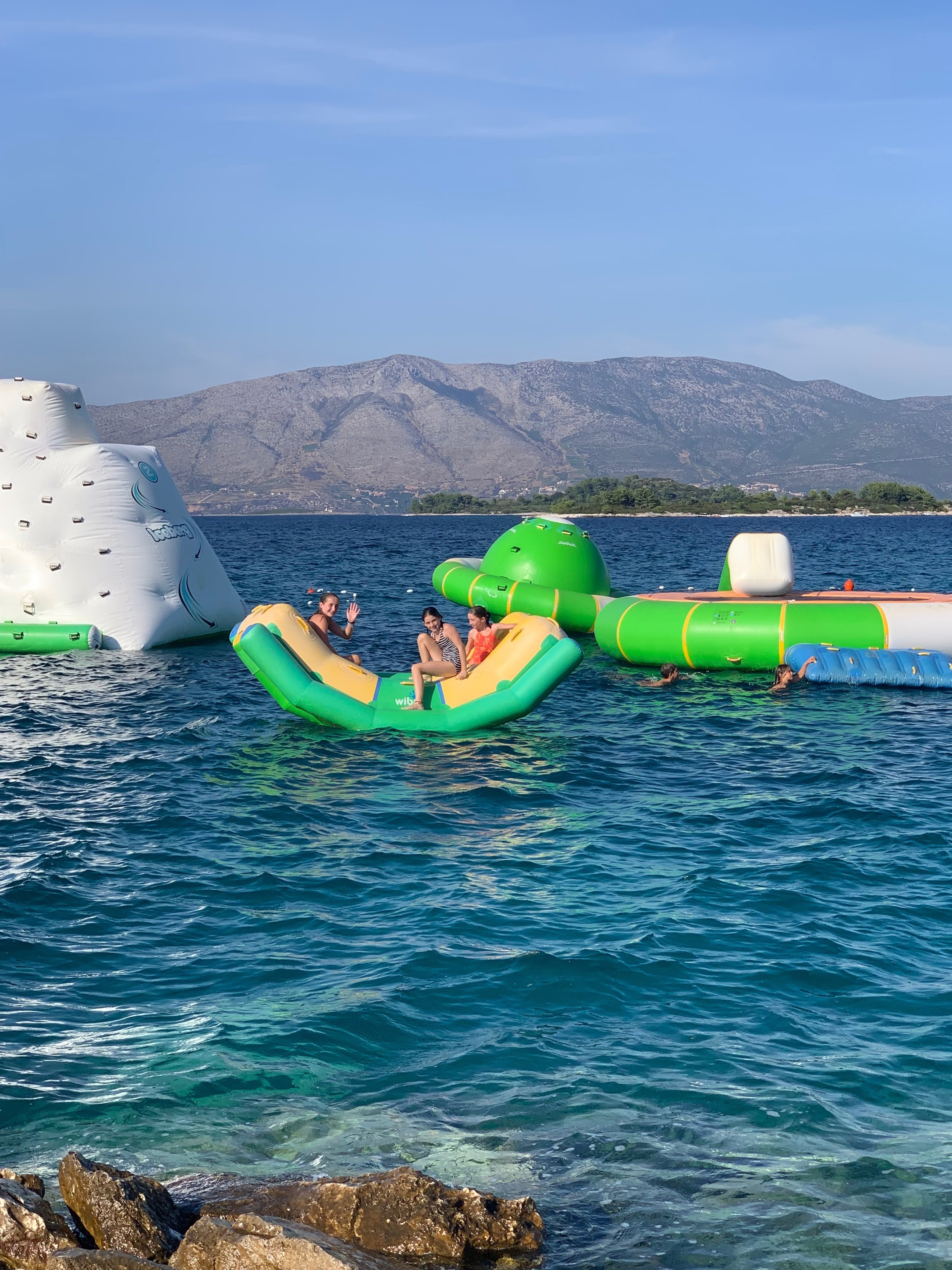 Necessary evil? The water trampoline park is probably best to give into right away, and then they'll forget about it!