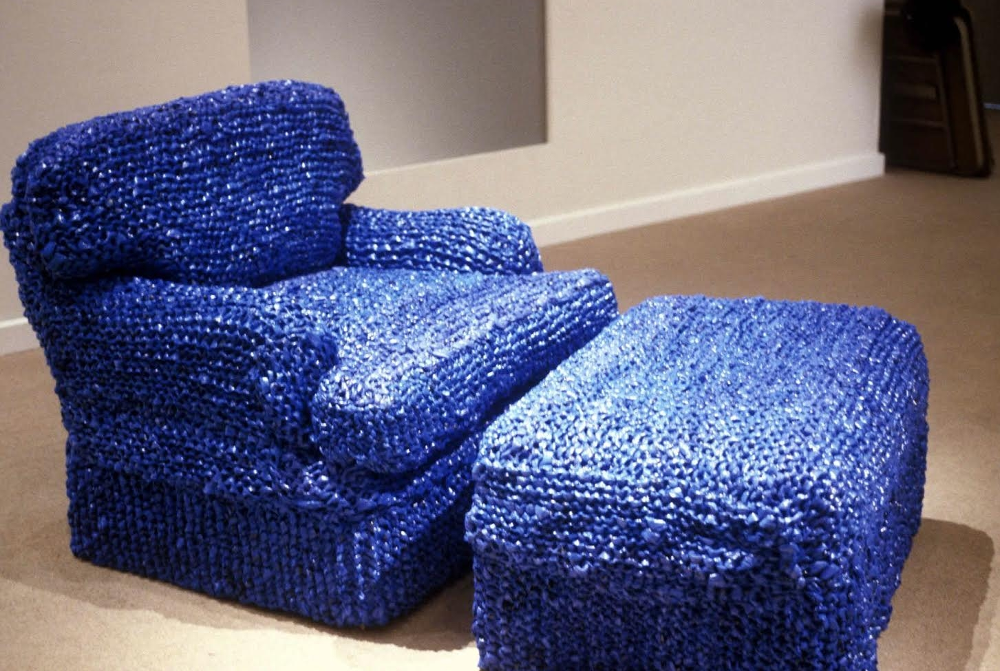 Sarah Hollis Perry - Teaches at the School of the Museum of Fine Arts, Boston and has a B.A. in Art History from Smith College, often employs skills associated with women's work such as weaving, knitting and sewing. This armchair, upholstered with New York Times delivery bags, provokes consideration of the annoying problem of overabundant bags.