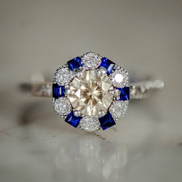 Now THIS is what dreams are made of 🙌😭 . This engagement ring is unlike any other Art Deco ring our shop has acquired! Boasting a total 1.02 ctw of stones, this piece features a center champagne diamond with a halo of alternating bezel-set round brilliant diamonds and square baguette sapphires. The icing on the cake? The entire shank is perfectly hand etched for added sparkle! . Click to window-shop or purchase, and be sure to follow @revivalrings for your daily dose of lovely! 🎁💕 . . . #revivalstudioco #revivalrings #haloring #antiquejewelryaddiction #showmeyourring #artdeco #artdecoring #artdecojewelry #artdecoengagementring #artdecostyle #sapphirering #hexagonring #hexagon #champagnediamonds #champagnediamond #browndiamond #cognacdiamond #showmeyourrings #antiqueshops #antiquejewels #antiquejewelry #antiquejewelryaddiction #antiquejewelryforsale #jewelrygram #jewelryaddict #jewelryforsale #engagementring #dreamring #engagementringideas
