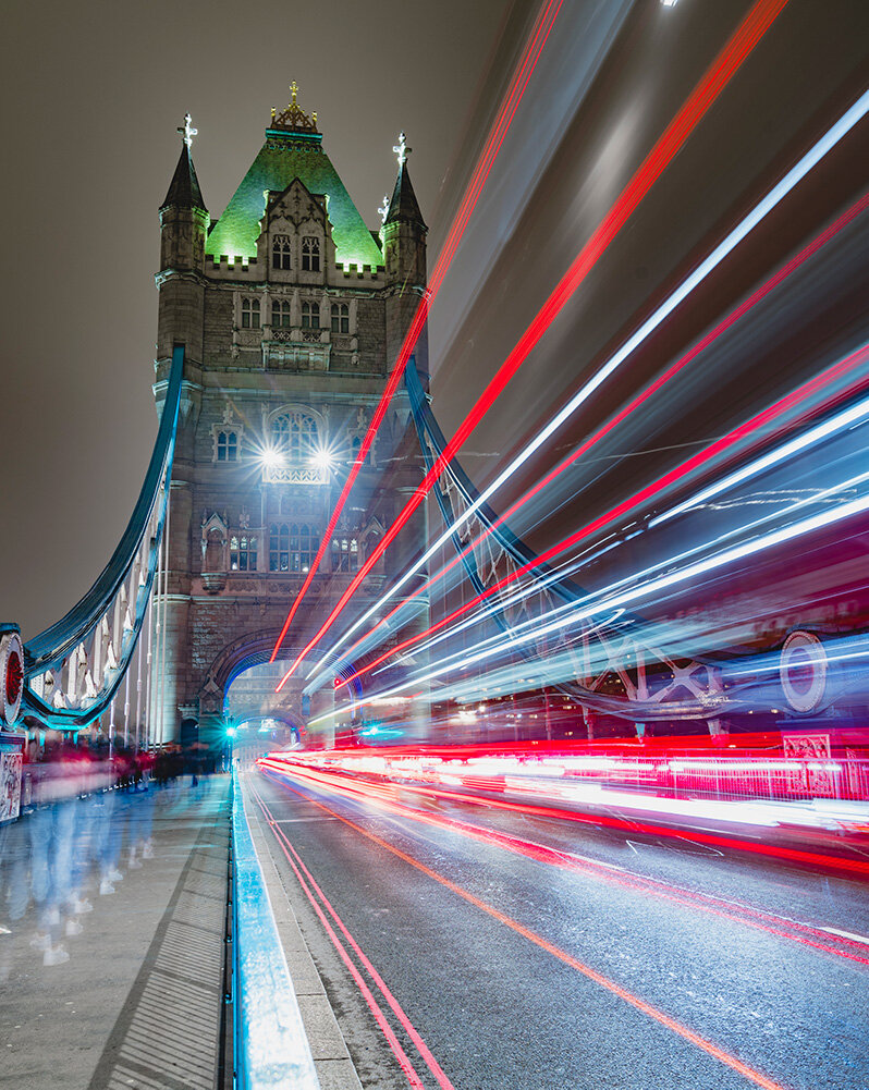 Long exposure image of Tower Bridge at night with light trails from a bus driving across.