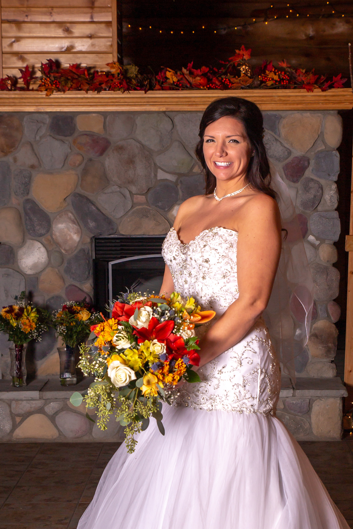 Glenhaven winter Minnesota wedding rustic barn, orange and yellow bouquet, in front of stone fire place