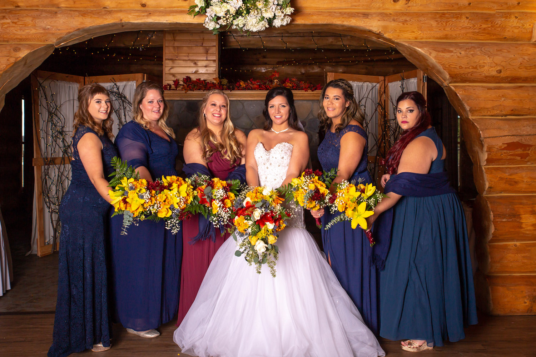 Glenhaven winter Minnesota wedding rustic barn, orange and yellow bouquet, bridesmaids in navy and burgundy