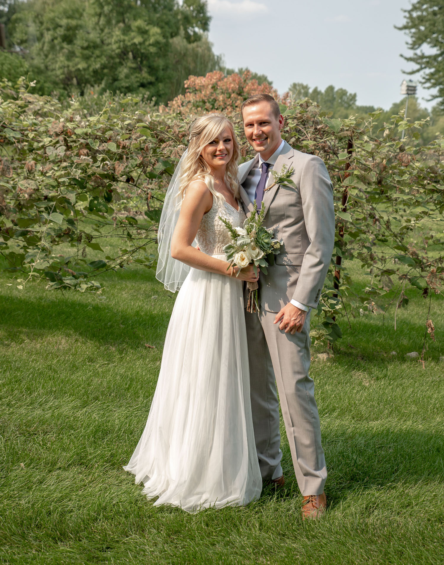 Cindyrellas Garden outdoor wedding ceremony by a private lake with wooded backdrops, hydrangea