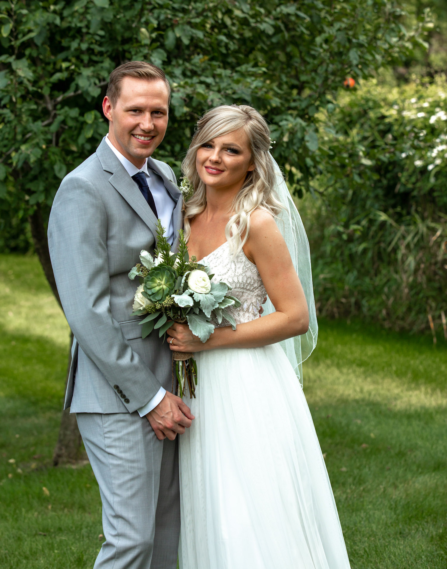 Cindyrellas Garden outdoor wedding ceremony by a private lake with wooded backdrops, simple bouquet