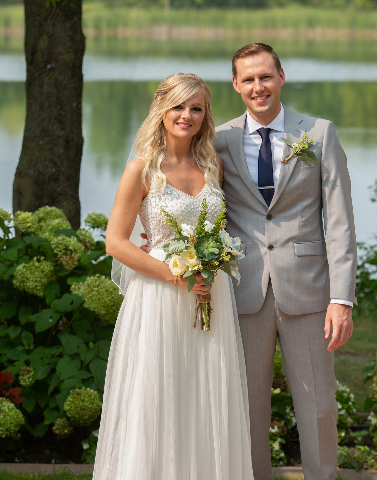 Cindyrellas Garden outdoor wedding ceremony by a private lake with wooded backdrops, bride in beaded top dress