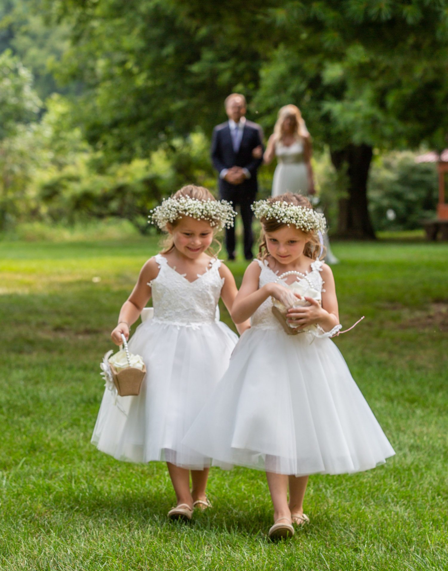 Cindyrellas Garden outdoor wedding ceremony by a private lake with wooded backdrops, queen anne's lace crowns on flower girls