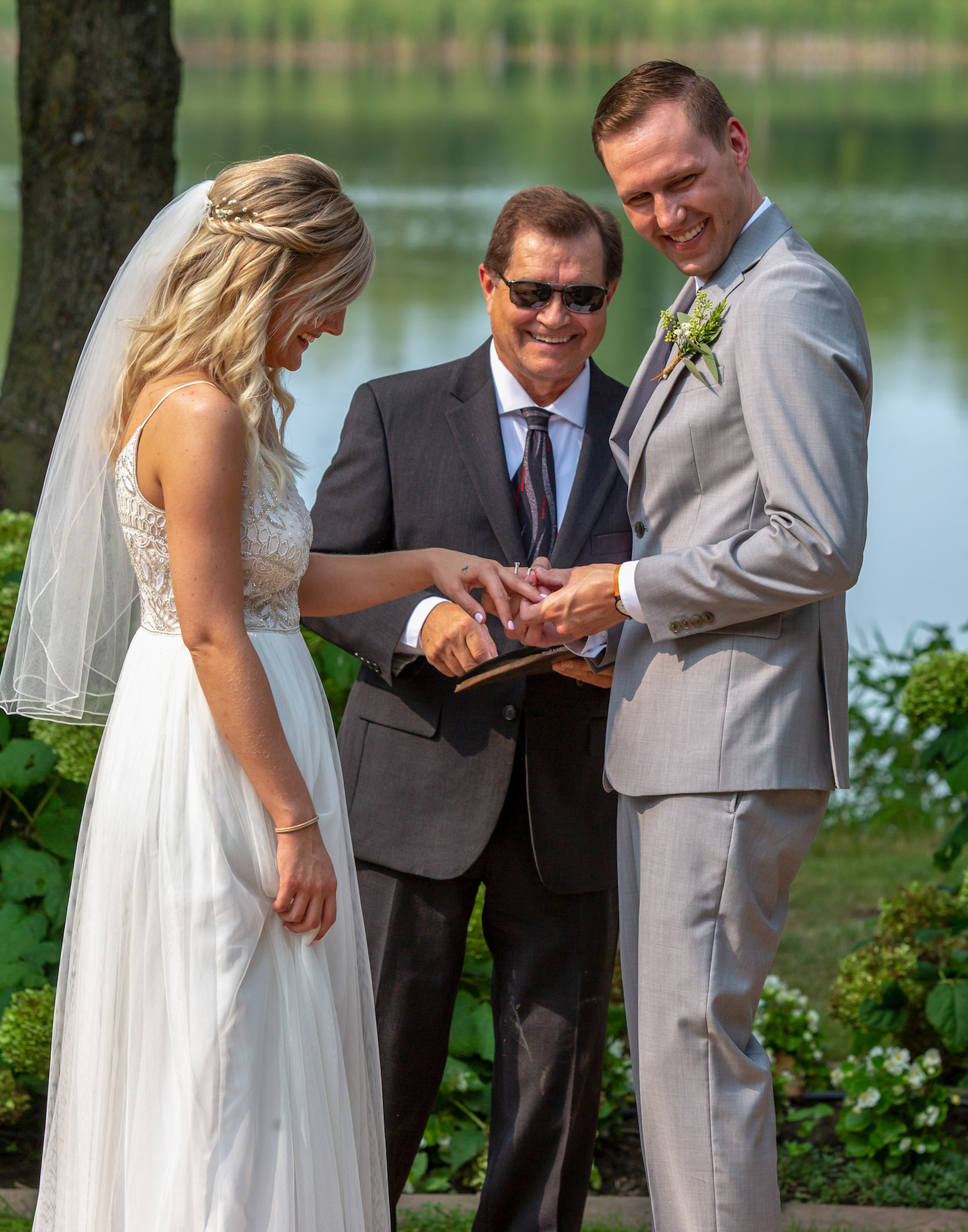 Cindyrellas Garden outdoor wedding ceremony by a private lake with wooded backdrops, ring exchange photo