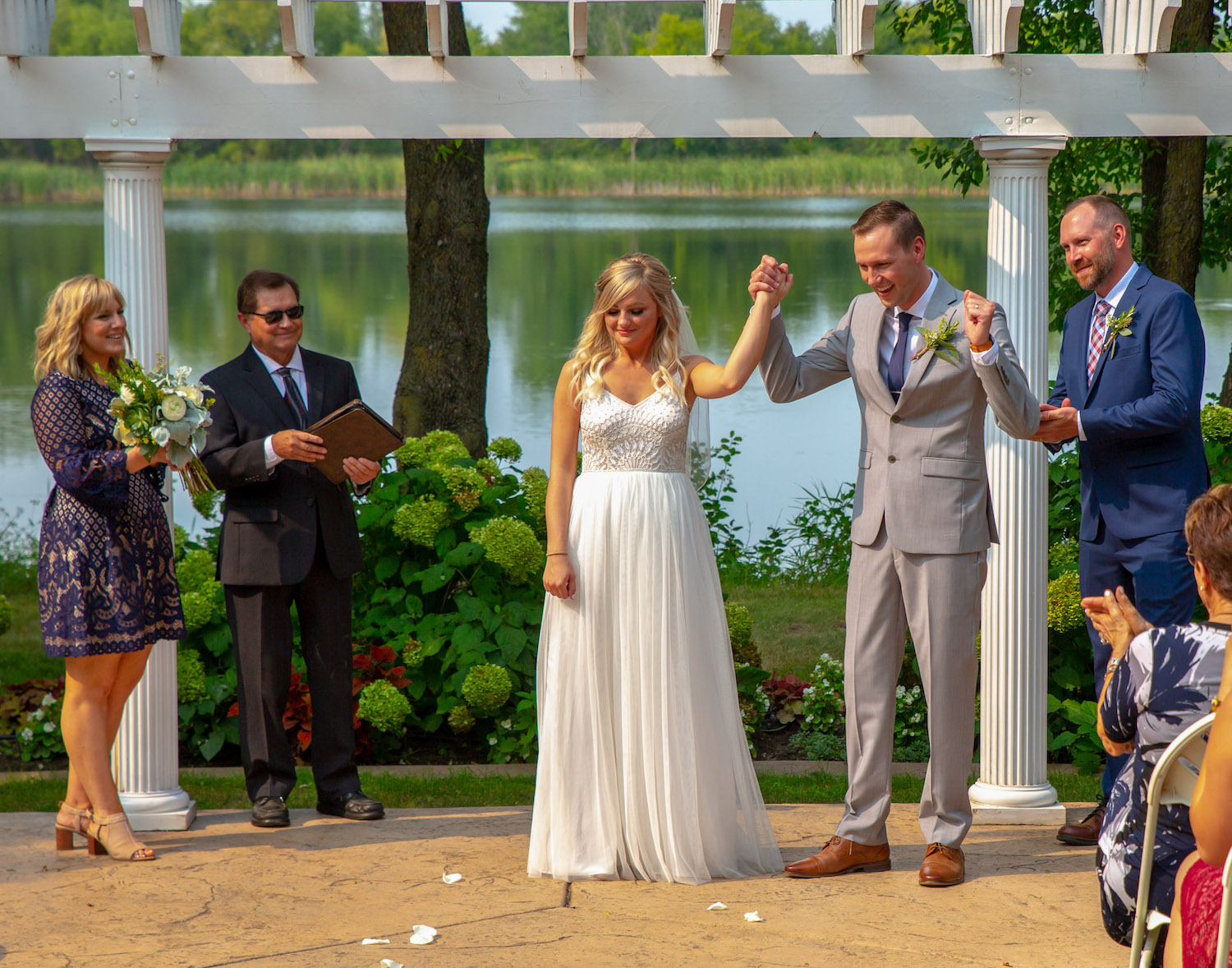 Cindyrellas Garden outdoor wedding ceremony by a private lake with wooded backdrops, just married