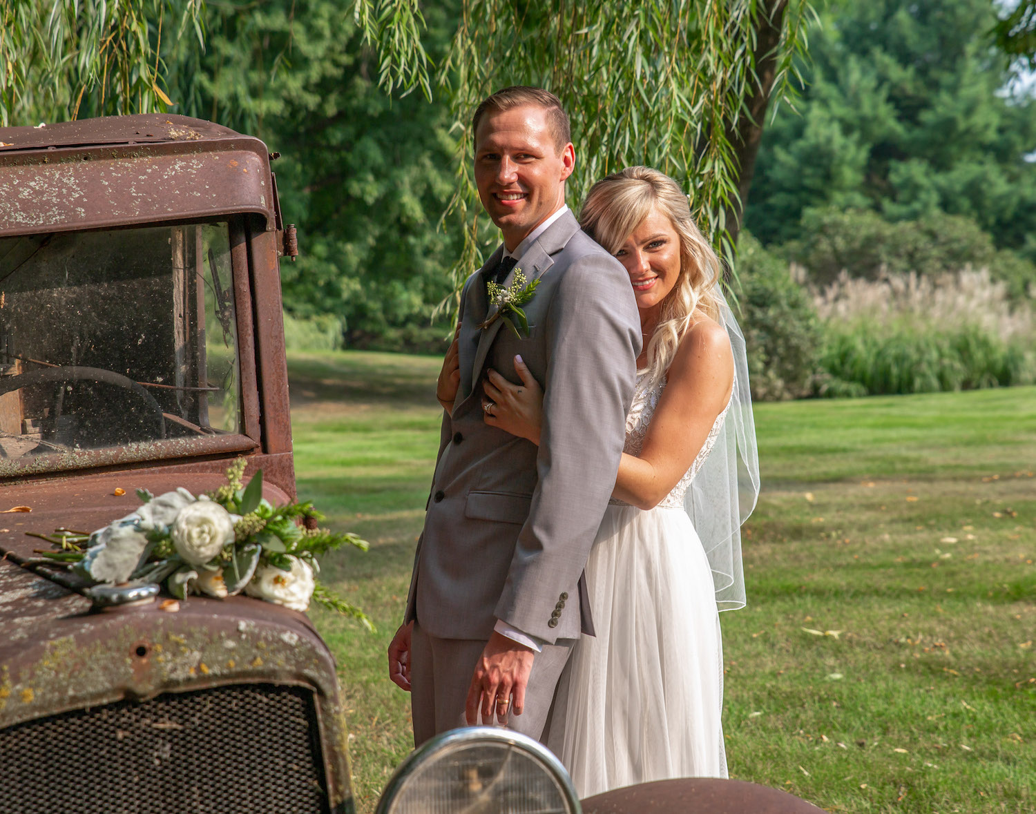 Cindyrellas Garden outdoor wedding ceremony by a private lake with wooded backdrops, hugging photo