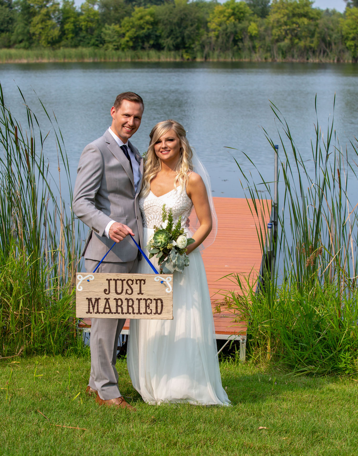 Cindyrellas Garden outdoor wedding ceremony by a private lake with wooded backdrops, just married sign