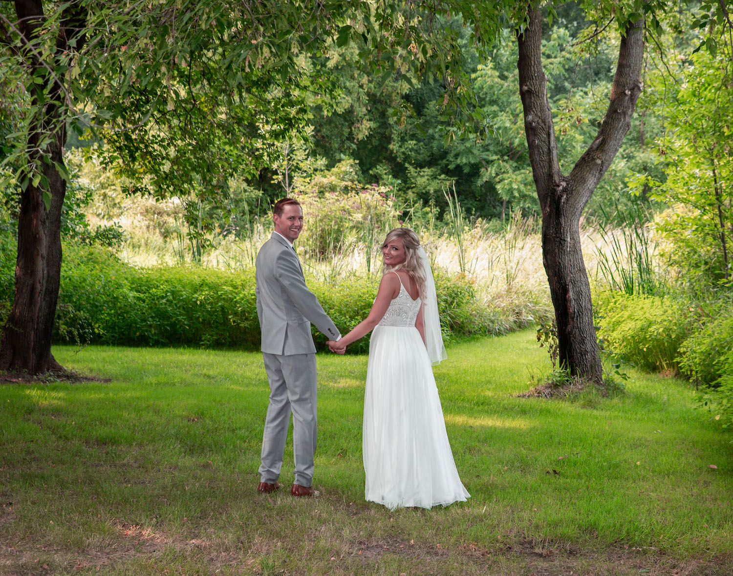 Cindyrellas Garden outdoor wedding ceremony by a private lake with wooded backdrops, elegant bride