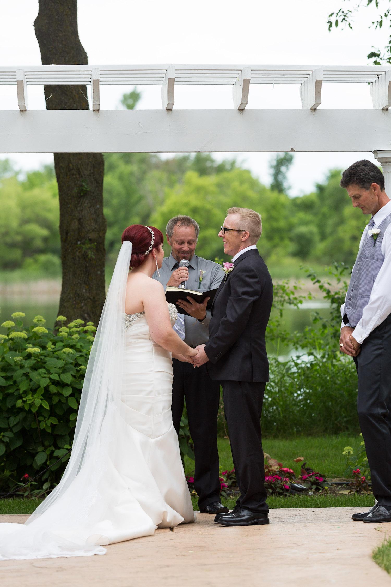 Cindyrella's Garden outdoor ceremony by the lake with a redhead bride, bride hair piece