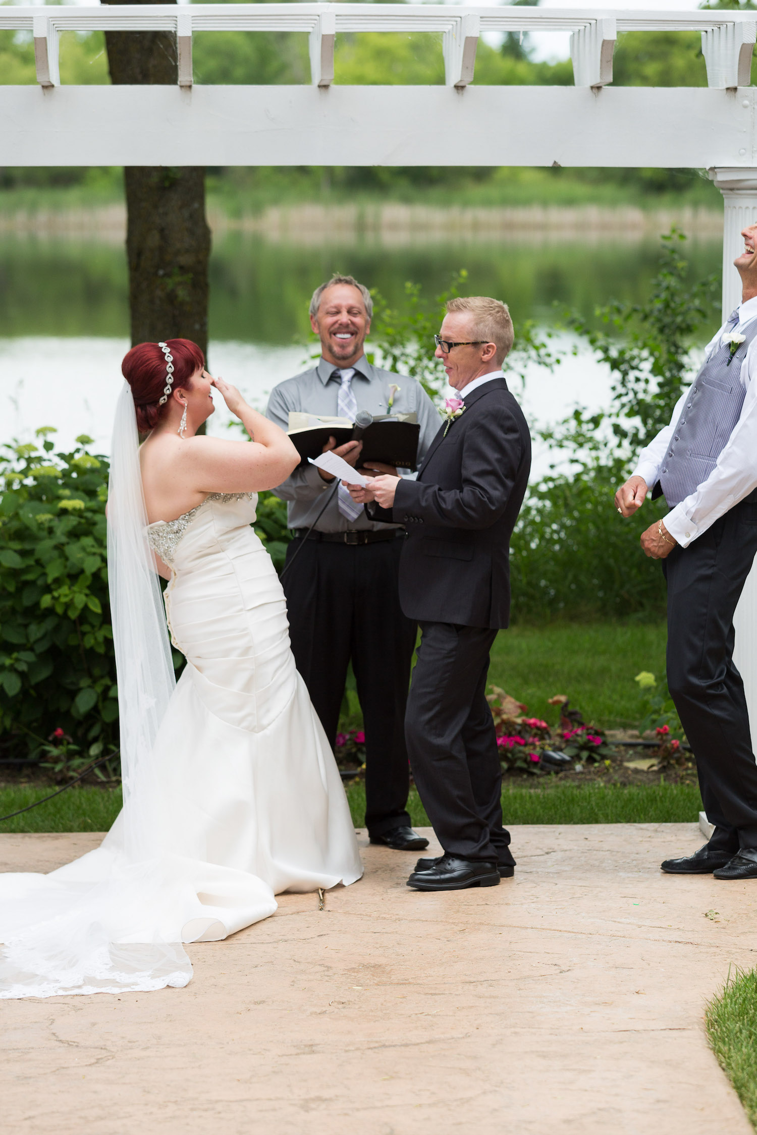 Cindyrella's Garden outdoor ceremony by the lake with a redhead bride, laughing