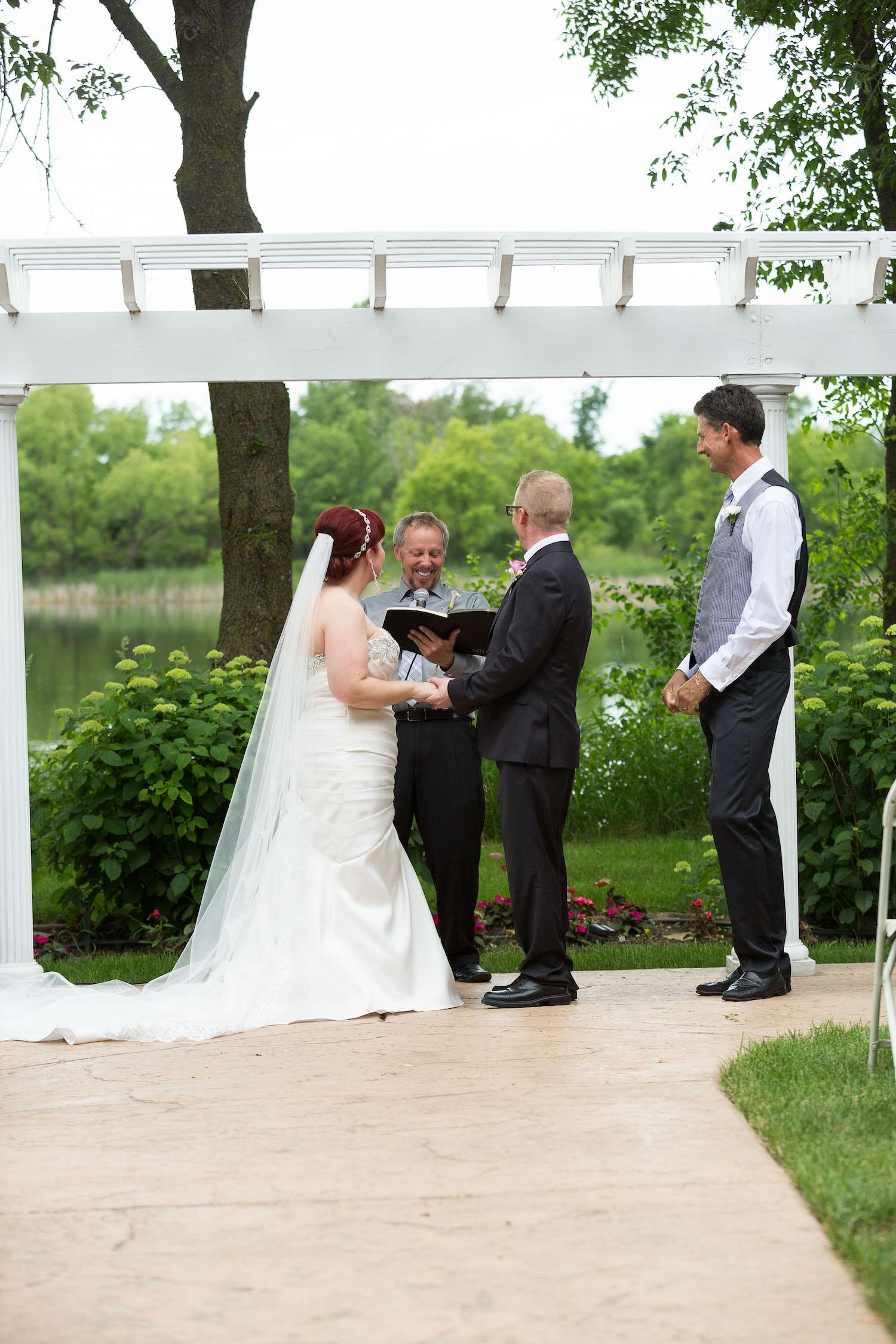 Cindyrella's Garden outdoor ceremony by the lake with a redhead bride,