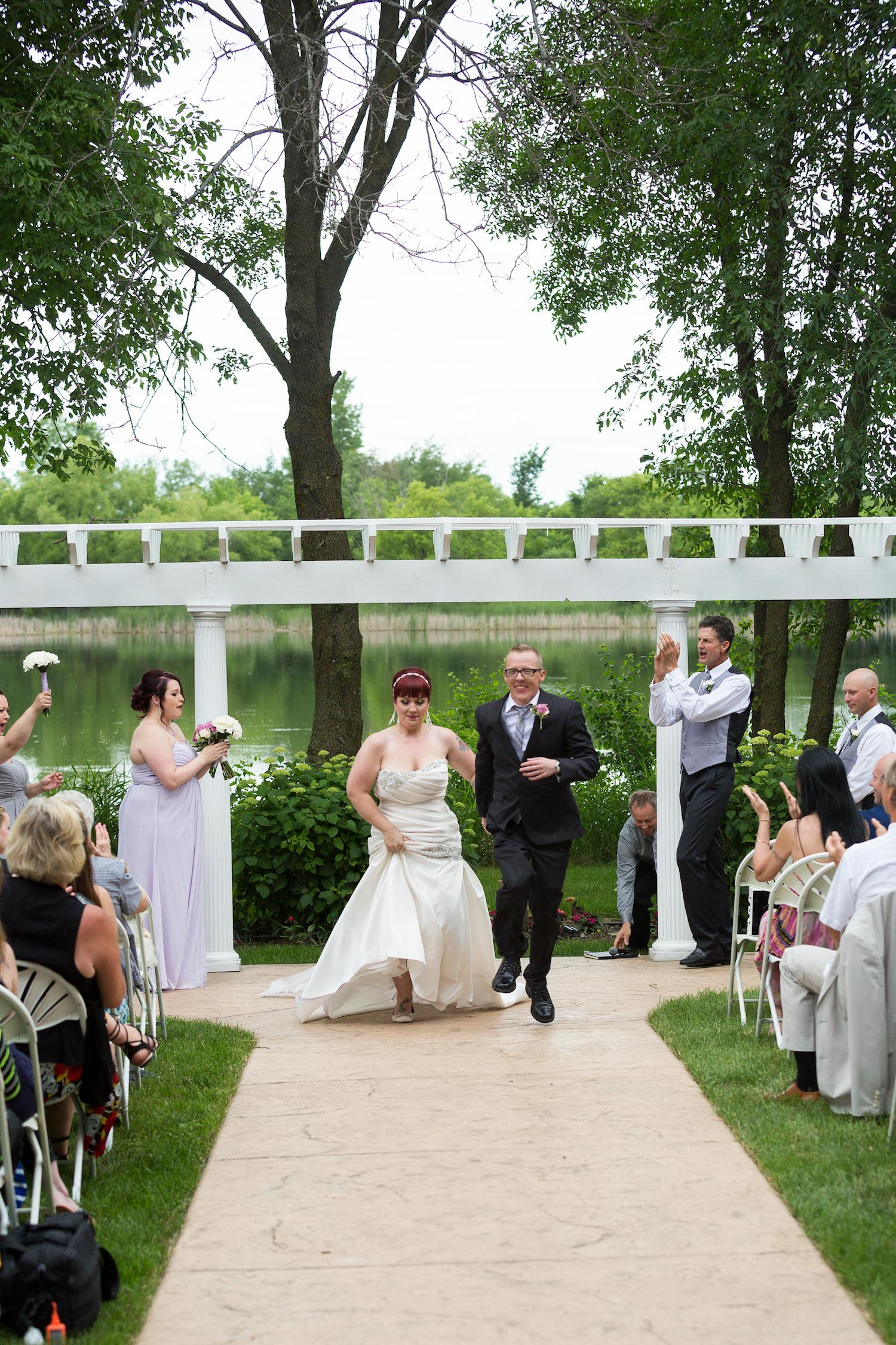 Cindyrella's Garden outdoor ceremony by the lake with a redhead bride, skipping down the aisle
