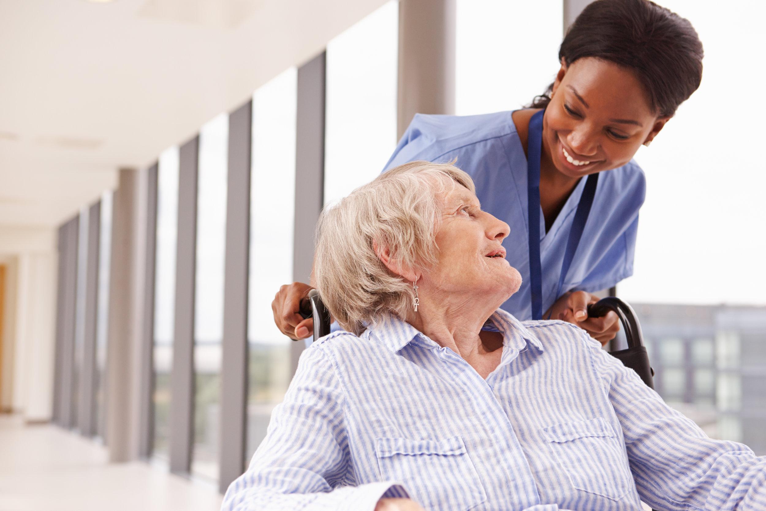 Nurse-Pushing-Senior-Patient-In-Wheelchair-Along-Corridor-488756218_4992x3328.jpeg