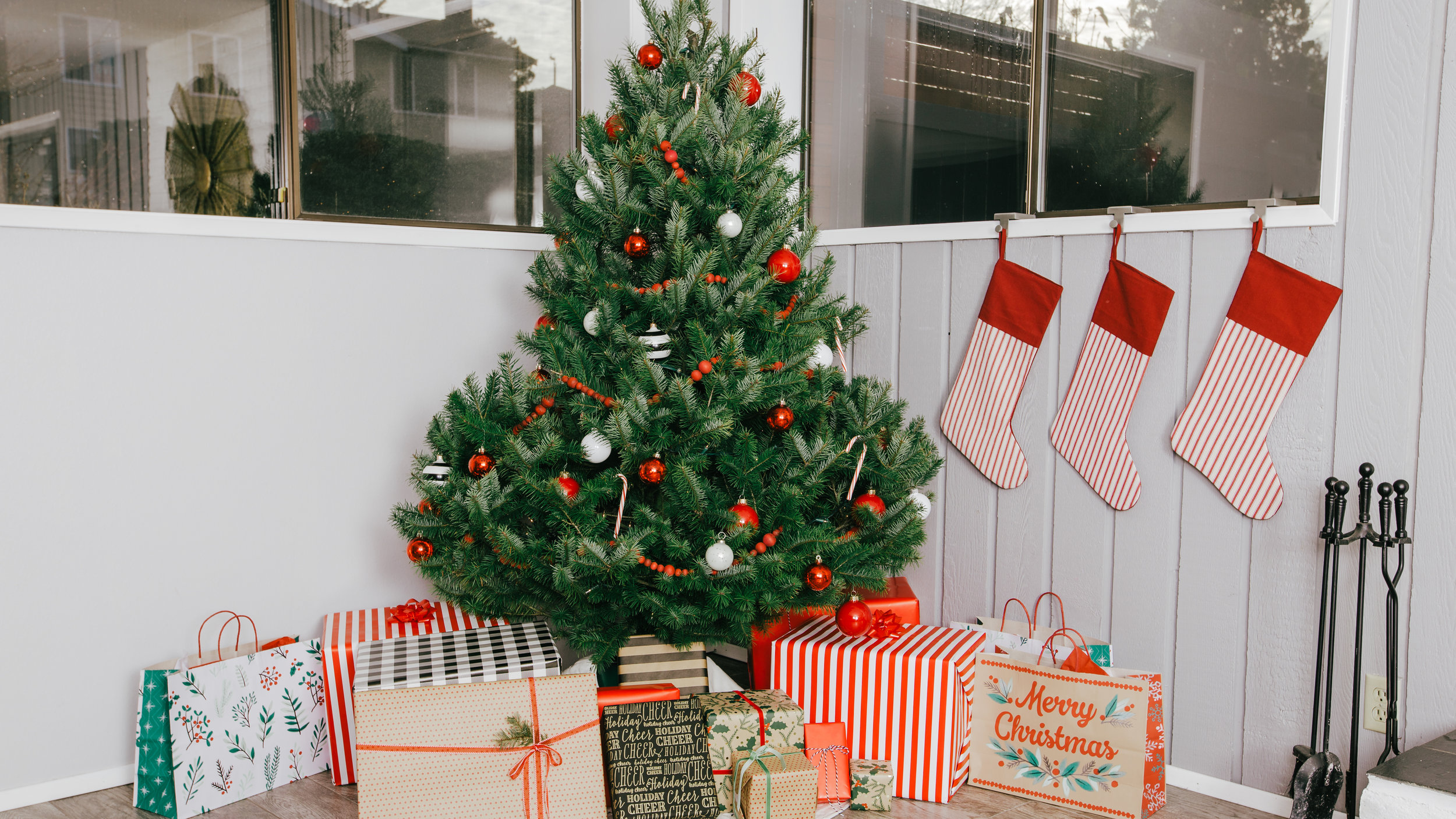 Christmas tree outside of tent/in seating area. Tree decorated w/twinkle lights and red/white ornaments. Wrapped packages under the tree. Tree will either be in a galvanized metal bucket, or will have a burlap/plaid skirt at the base.