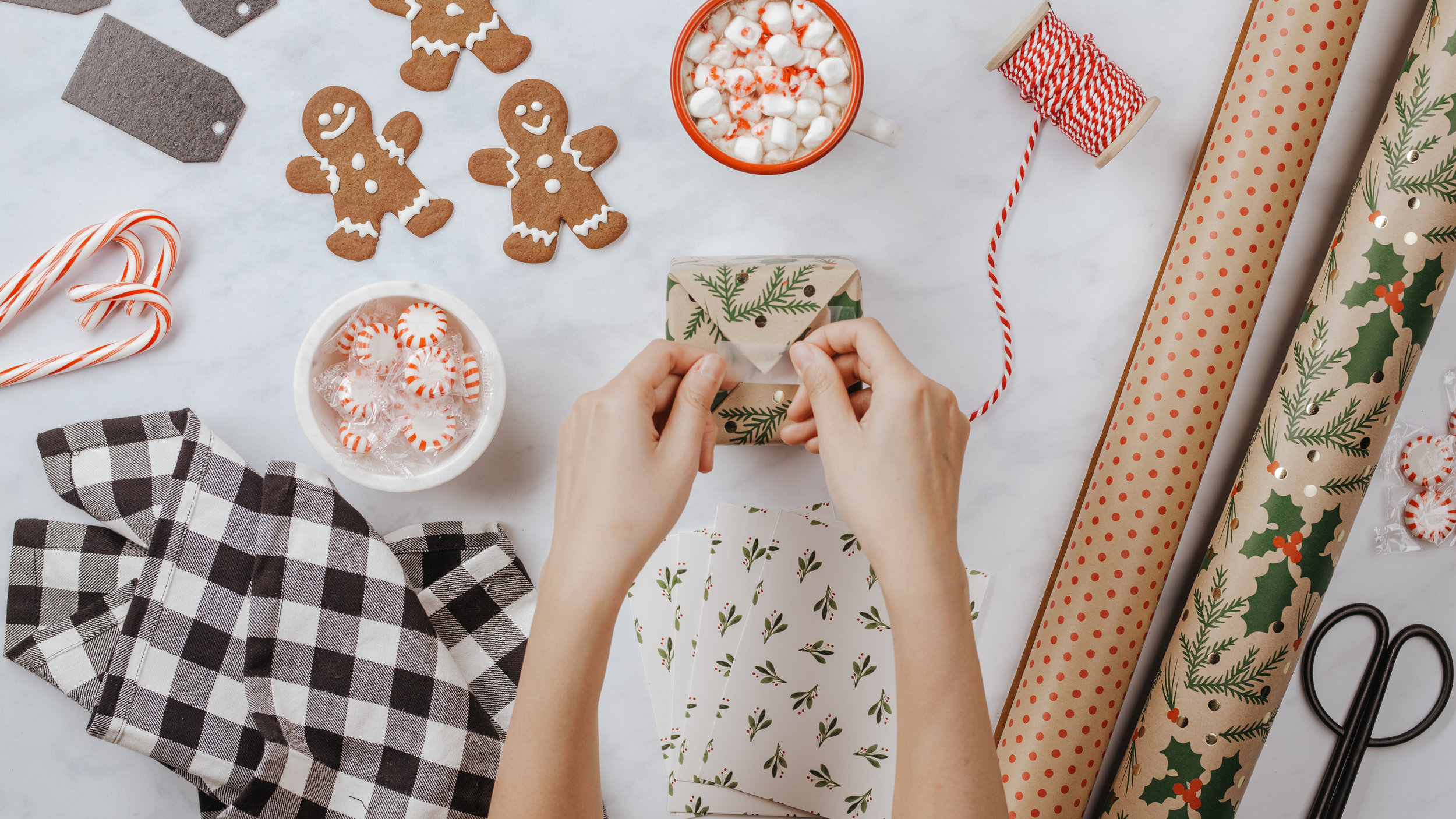 Gift-giving flatlay (flatlay layout will be customized to the Woods Christmas set - items like a plate of peppermint cookies, 2 mugs of cocoa, candy canes, mittens, ornaments, greenery, etc. will be featured.)