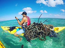 Kayaker Picking Up Old Fishing Net