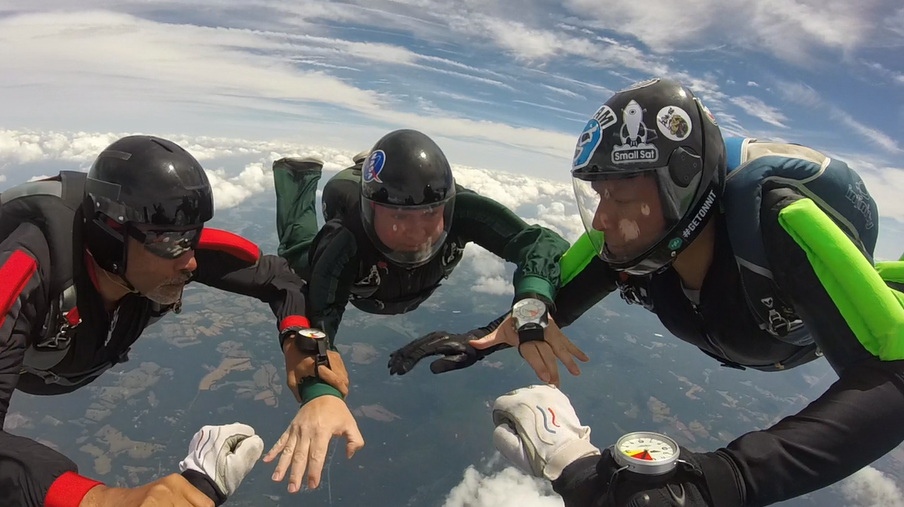 Eli (far right) builds a base on an 8-way relative work formation skydive.  Photo courtesy of Erin Kruth.