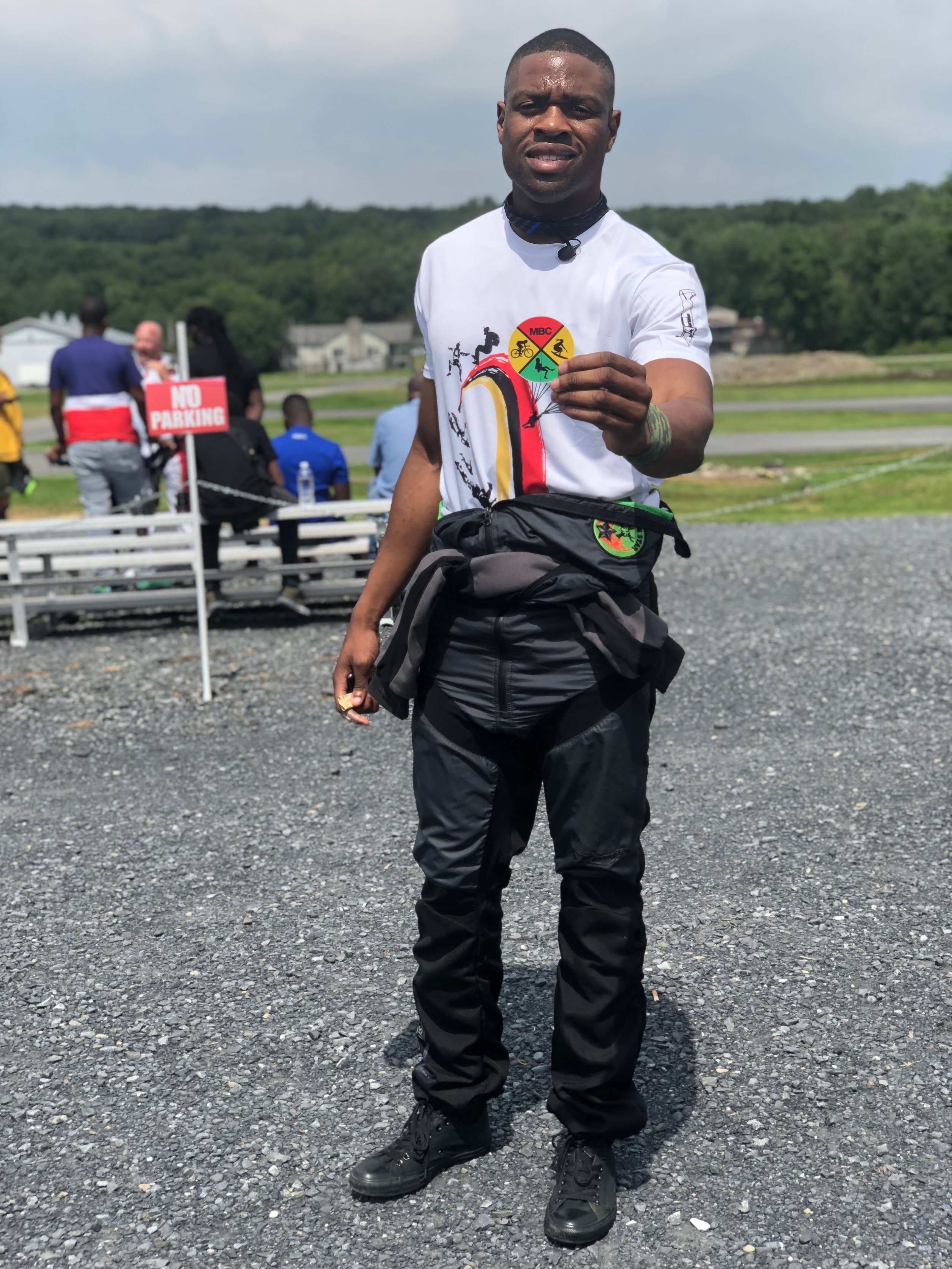 Manny sports a Team Blackstar patch on his jumpsuit while also holding up a Melanin Base Camp sticker. Both organizations promote diversity in adventure sports.  Photo courtesy of Cyndall King
