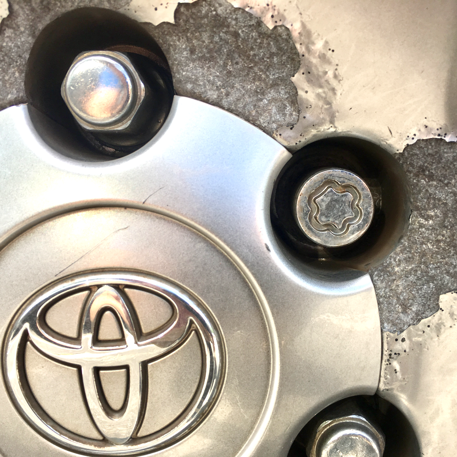 A locking lug nut flanked by two standard lug nuts. If your car has locking lug nuts make SURE you have the key to remove them.