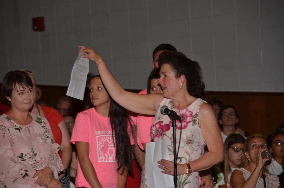"""The DRRSD Foreign Language Department shows the crowd at the June 12th, 2018 DRRSD School Committee Meeting what a """"pink slip"""" really looks like."""