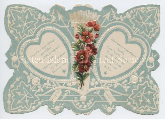 Greeting card (probably a valentine); folded and die-cut paper with hearts, flowers and arrows in blue and white, with applied die-cut flowers in shades of red and green.