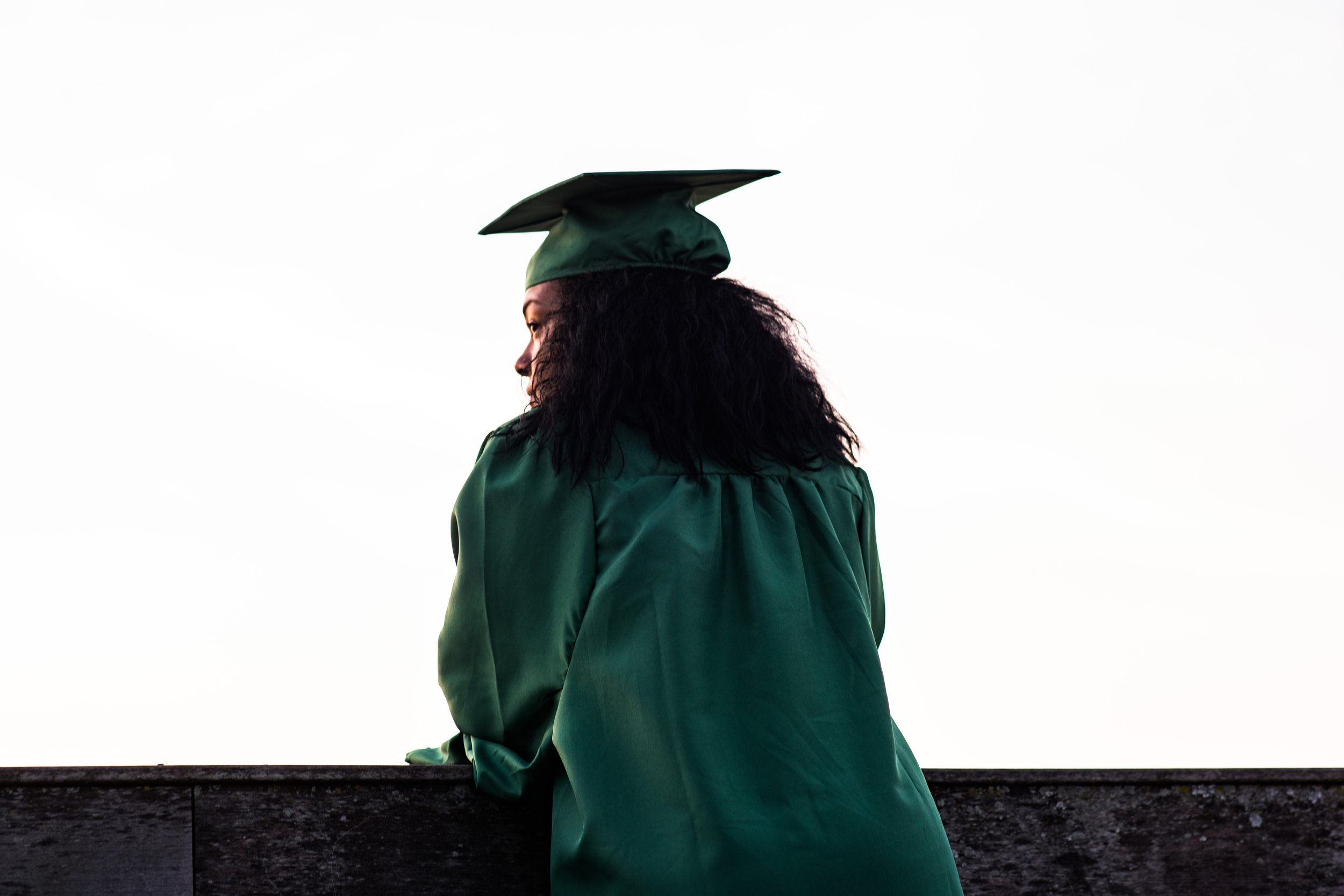 Image: Young woman in a graduation cap looking over ledge. Photo: Photo by  Andre Hunter  on  Unsplash